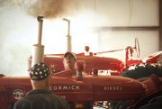 "Greg Coker, president of Kansas chapter 3 of International Harvester Collectors watches smoke billow from the exhaust of a 1953 McCormick Super WD6 tractor as it's started in the garage of Douglas County resident Judy Pierson. Almost 30 tractors from the 1940s, '50s and '60s were moved from Pierson's farm Wednesday morning. All of them, which will be auctioned this weekend at the Johnson County Fairgrounds in Gardner, were restored by Pierson's husband, John Pierson, a Douglas County resident who died in 2008 of complications from pancreatic cancer. ""He loved working on old engines. He could make anything run."""