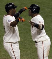San Francisco's Edgar Renteria, left, and Juan Uribe celebrate after scoring during the Giants' seven-run eighth inning of Game 2 of the World Series. The Giants won, 9-0, for a 2-0 lead in the series Thursday in San Francisco.