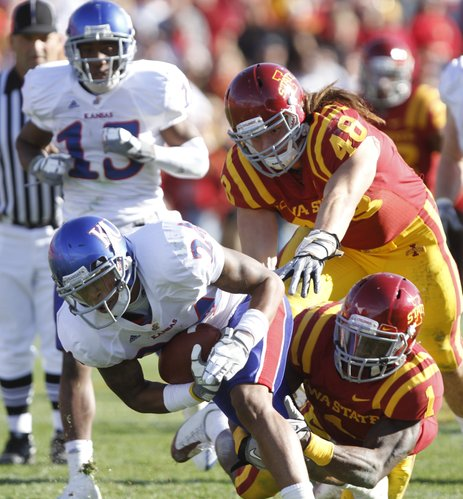 Iowa State defenders David Sims (1) and defensive end Jacob Lattimer pull down Kansas receiver Bradley McDougald after a reception by  during the fourth quarter Saturday, Oct. 30, 2010 at Jack Trice Stadium.