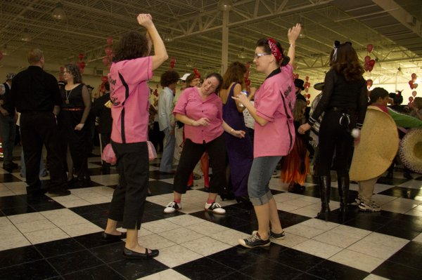 From left, Traci Wilson, Lawrence, Kendra Clouse, Lawrence, and Becky Bruitt, Tonganoxie, dance during the Stepping Out Against Breast Cancer dance held Oct. 30 at Crown Automotive. The dance raised money for the Lawrence Memorial Hospital's Endowment Association. Money raised will also further education and community outreach for early detection programs.