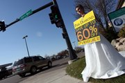 To attract customers, some small businesses plant employees near their business often dressed in costume, holding a sign, which the employee shakes to attract drivers's attention. Here, sporting a wedding dress, Briton Tomasko, 18, granddaughter of the owners of Park Diamond, tried to drum up business in Maplewood, Minn.