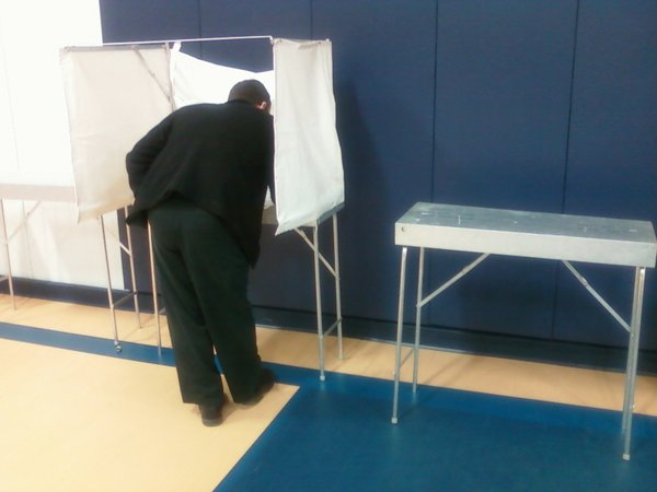 At least one voter avoided the falling canvas at a polling site Tuesday in Douglas County. At right is a both where the canvas already had fallen.