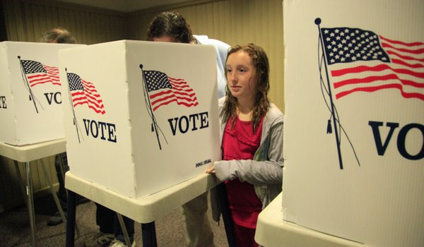Eliana Seidner 10, watches the activity at the Union Pacific Depot polling place while waiting for her mother to cast her vote Tuesday morning.