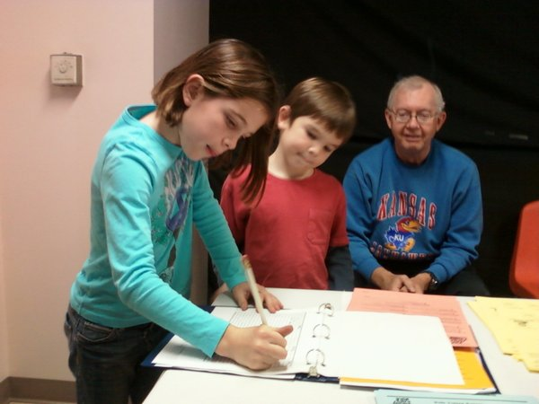 Erin Fagan and her brother, Max Fagan, sign the registration book before casting their unofficial ballots at Southside Church of Christ. At right is Dick Shaffer, their grandfather, who had voted earlier Tuesday. Erin and Max are among youngsters voting countywide through Kids Voting.