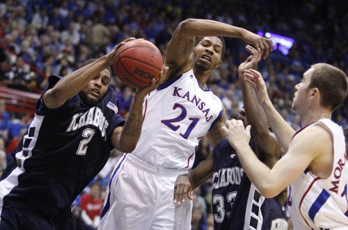 Kansas forward Markieff Morris (21) swipes at the ball as it's pulled down by Washburn forward De'Andre Washington (2) in the first half of the exhibition game, Tuesday, Nov. 2, 2010 at Allen Fieldhouse. Also pictured are Washburn guard Nate Daniels (33) and Kansas guard Brady Morningstar (12).