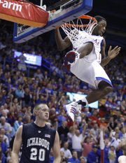 Kansas guard Elijah Johnson takes his time coming down from the rim after finishing off an alley-oop dunk against Washburn in the second half of the exhibition game, Tuesday, Nov. 2, 2010 at Allen Fieldhouse. At bottom is Washburn forward Bobby Chipman.