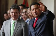 Venezuela's President Hugo Chavez, right, waves to journalists Tuesday as Colombia's President Juan Manuel Santos looks on after a welcoming ceremony at Miraflores presidential palace in Caracas, Venezuela.