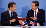French President Nicolas Sarkozy, left, and Britain's Prime Minister David Cameron exchange documents during the signing of a treaty at an Anglo-French summit Tuesday at Lancaster House in London. Britain and France vowed to work hand-in-glove as their leaders ushered in an unprecedented era of defense cooperation by agreeing to create a joint force and share nuclear test facilities.