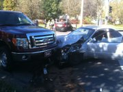 Two vehicles sit at the scene of a three-car accident on 23rd and Massachusetts streets while emergency crews tend to a patient in the background on Wednesday, Nov. 3, 2010.