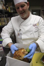 Lawrence Memorial Hospital's Chef Don Williams boxes up a hormone-free chicken.