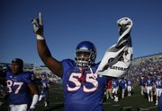 Kansas defensive tackle Darius Parish raises his hands before the fans following the Jayhawks' 52-45 win over Colorado, Saturday, Nov. 6, 2010 at Kivisto Field.