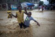 People wade through a flooded street during the passing of Hurricane Tomas on Friday in Leogane, Haiti.