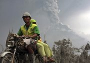 Villagers ride on a motorcycle Saturday as Mount Merapi spews volcanic materials in the background in Srumbung, Central Java, Indonesia.