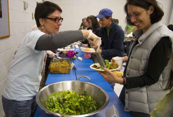 Deb Rake, left, serves Jean Trujillo salad that includes greens grown in the West Junior High School garden Saturday in the school's cafeteria. Trujillo attending a community dinner that celebrated the school's first garden project.