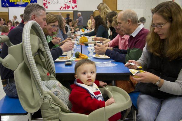 Emily Zung feeds her son Preston, 10 months, Saturday, Nov. 6, 2010, during a community dinner at West Junior High School. The dinner helped raise money for the school's garden project.