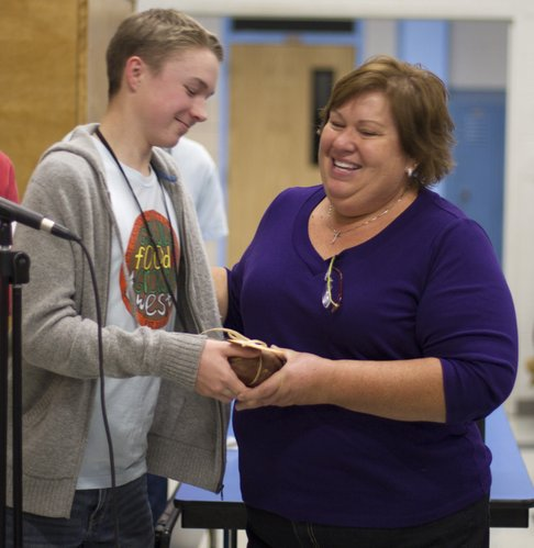 "West Junior High School student T.J. Everett, hands a ""Sweet Potato"" award to Bev Lockwood during a recognition ceremony Saturday evening at the school. Lockwood is the school's food service manager."
