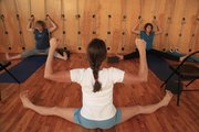 From left, Lisa Dahl, 43, and Emma Frosini, 22, get instructions on stretching from yoga instructor Kim Lacy at Yoga Center of Lawrence, 920 Mass.