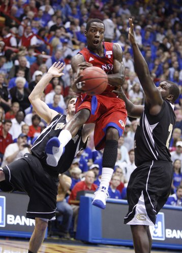 Kansas guard Tyshawn Taylor cuts through Emporia State defenders Taylor Euler, left, and Michael Tyler to throw a pass during the first half, Tuesday, Nov. 9, 2010 at Allen Fieldhouse.