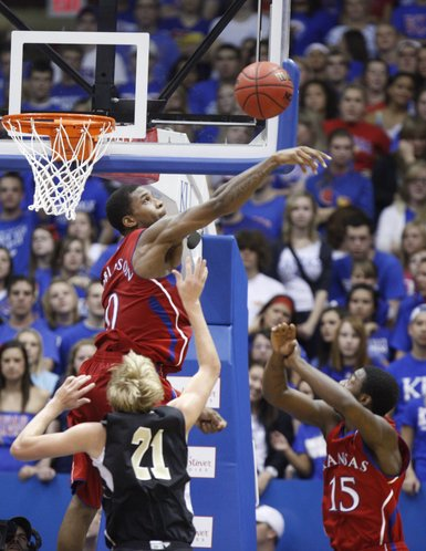 Kansas forward Thomas Robinson swats a shot by Emporia State forward Matt Boswell during the first half, Tuesday, Nov. 9, 2010 at Allen Fieldhouse. At right is Kansas guard Elijah Johnson.