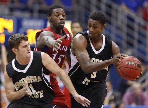 Kansas guard Elijah Johnson defends as Emporia State guard Jarvis Nichols (3) tries to hand off to Taylor Euler (11) during the first half, Tuesday, Nov. 9, 2010 at Allen Fieldhouse.