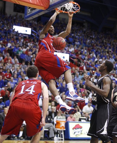 Kansas forward Marcus Morris throws down a dunk against Emporia State during the first half, Tuesday, Nov. 9, 2010 at Allen Fieldhouse. At left is KU guard Tyrel Reed and at right is ESU guard Jarvis Nichols.