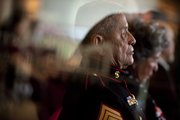 "Viewed through glass doors at the Dole Institute of Politics, Sgt. Maj. Jess Pacheco, retired, a Marine Corps veteran of World War II, the Korean War and Vietnam, listens to a speech emphasizing the important sacrifices of service members by retired Navy Capt. John W. ""Buck"" Newsom during the 235th birthday celebration for the United States Marine Corps on Wednesday. Pacheco, the oldest marine present at Wednesday's celebration, joined the Marine Corps in 1943 and served until his retirement in 1979."
