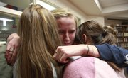 Lawrence High swimming senior Emma Reaney, center, hugs classmates at LHS. Reaney signed her letter of intent to swim at Notre Dame on Thursday at LHS.