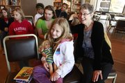 Eila Deavours, 8, Lawrence, holds her American Girl doll as Lawrence author Jane Kurtz, right, talks with children at the Kansas Union on Saturday.