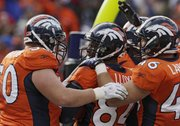 Denver wide receiver Brandon Lloyd (84) is congratulated by teammates after a six-yard touchdown catch. The Broncos beat the Chiefs, 49-29, Sunday in Denver.