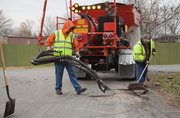 City of Lawrence street crews use a new machine Wednesday that repairs potholes with a method called spray injection patching. The method, which also is used by the Kansas Department of Transportation, allows the city to make lasting fixes to potholes during winter.