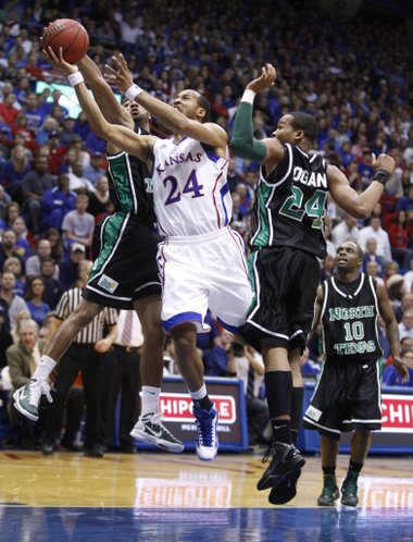 Kansas guard Travis Releford cuts through North Texas defenders Shannon Shorter, left, and Kedrick Hogans during the first half, Friday, Nov 19, 2010 at Allen Fieldhouse. In back is North Texas guard Josh White. Releford was fouled on the play.