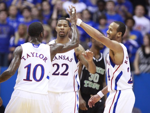 Kansas teammates Tyshawn Taylor, Marcus Morris (22) and Travis Releford come together for high fives during the second half Friday, Nov 19, 2010 at Allen Fieldhouse.