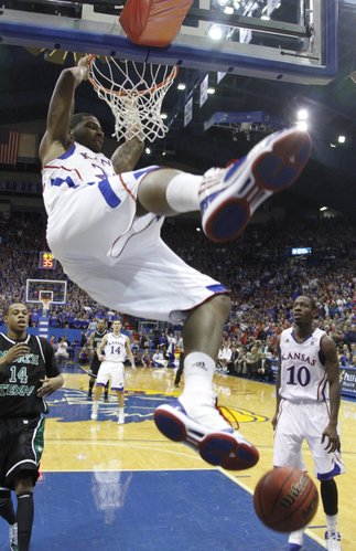 Kansas forward Marcus Morris swings off the rim after delivering a dunk against North Texas during the second half Friday, Nov 19, 2010 at Allen Fieldhouse.