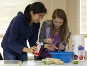 Yihaw Li, left, and Lisa Volkin, both freshmen at Southwest Junior High School, measure salt as they make pie crusts for the LINK Thanksgiving dinner.