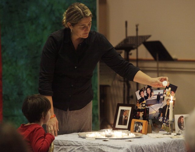 Karen Dillon, of Vinland, lights a candle to remember her son, Dakota Dillon Pite, who died by suicide. Her daughter, Annabel, 5, also lights a candle to remember her older brother. They were among about 30 people who participated in a National Survivors of Suicide event Saturday, Nov. 20, 2010, at First United Methodist Church in downtown Lawrence.