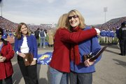 Kansas University journalism lecturer and this year's HOPE Award winner Denise Linville, right, gets a hug from fellow finalist and journalism lecturer Kerry Benson during Saturday's home football game. The senior class nominated five KU faculty members as finalists for this year's award. At left is finalist Tara Welch, associate professor of classics.
