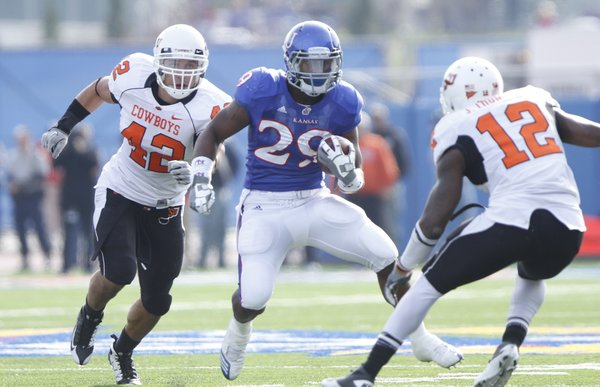 Kansas running back James Sims looks to put a move on Oklahoma State safety Johnny Thomas (12) during the second quarter, Saturday, Nov. 20, 2010 at Kivisto Field. In back is OSU linebacker Justin Gent.