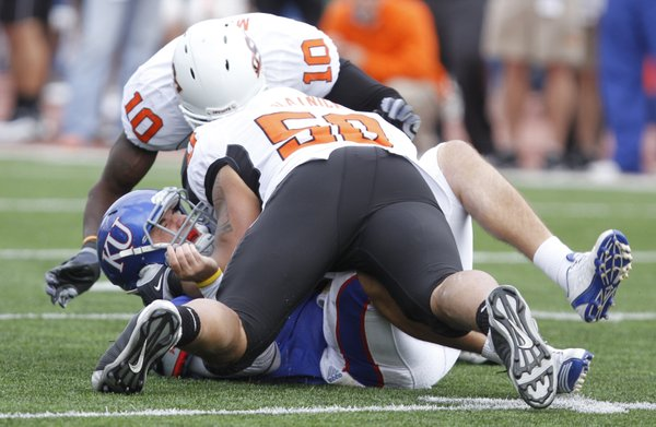 Kansas quarterback Quinn Mecham is driven to the turf on a sack by Oklahoma State defensive end Jamie Blatnick (50) during the third quarter, Saturday, Nov. 20, 2010 at Kivisto Field. Also assisting on the stop is OSU safety Markelle Martin.
