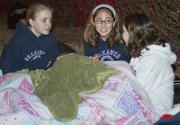 Huddled under blankets to keep warm on a chilly November night, Bishop Seabury freshmen, from left, Aine McGrath, 14, Alicia Cotsoradis, 14 and Courtney Cooper, 14, tell stories as they spend the night outdoors on the front lawn of Bishop Seabury school Sunday evening as part of a sleep in blanket service event. The students were only allowed two blankets each. The event aimed to raise food donations.
