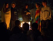 Huddled around a fire to keep warm, Bishop Seabury students spend the night outdoors on the front lawn of Bishop Seabury Academy Sunday. The students were each only allowed two blankets. The event was held to raise food donations.