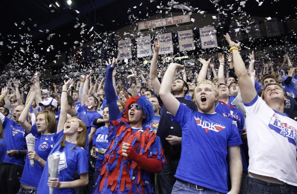 Kansas University students Kaylan Conner, Shawnee sophomore, left of center, Armand Heyns, Topeka senior, and Carmeron Bernard, Topeka junior erupt with confetti in the student section as the Jayhawks' starting lineup is announced before tipoff against Texas A&M-Corpus Christi, Tuesday, Nov. 23, 2010 at Allen Fieldhouse. These three joined the boisterous Fieldhouse crowd to help cheer the Jayhawks to their record-setting, 63rd-consecutive home victory.