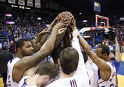 Kansas forward Markieff Morris, left, and his teammates come together over a game ball presented after their 82-41 victory over Texas A&M-Corpus Christi, Tuesday, Nov. 23, 2010 at Allen Fieldhouse. The win set the record for the most consecutive home wins by a Jayhawk team at 63.