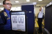 Transportation Security Administration screener Marlon Tejada, left, watches as Randy Parsons, TSA acting Federal Security Director, right, goes through a full body X-ray scanner for a security screening Monday at the Los Angeles International Airport.