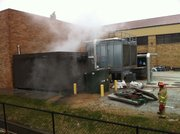 Fire crews tend to smoke at the Anschutz Sports Pavilion on the Kansas University campus on Tuesday, Nov. 23, 2010. 