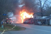 A firefighter stands in front of a burning home on U.S. Highway 40 near the Shawnee County line on Wednesday, Nov. 24, 2010.