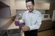 Professor George Wang holding a purple sweet potato.