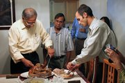 Swapan Chakrabarti carves the Thanksgiving turkey while Dhananjay Pal watches and Joe Sambataro cuts it into smaller pieces. Chakrabarti, an associate professor of electrical engineering at Kansas University, was at Pal's home for a Bengali Thanksgiving, complete with American favorites such as turkey, plus traditional Indian foods.