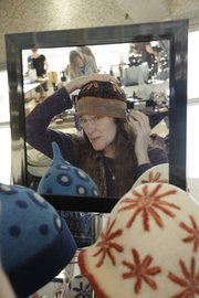 Trying on a hat, Alison Roepe, Lawrence, shops on Black Friday at the Fair Trade Holiday Market at Ecumenical Christian Ministries, sponsored by the Lawrence Fair Trade Coalition. Shoppers found items at the market from all over the world.
