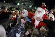 After being rescued from the roof at Weaver's, Santa hands out candy to children on Massachusetts Street. The holiday season officially kicked off Friday night as the Christmas lights along Massachusetts Street were switched on.