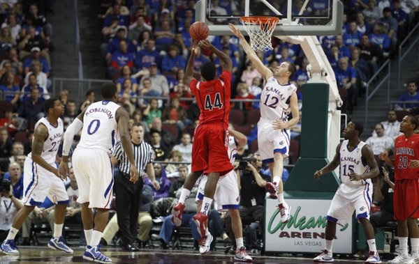Kansas guard Brady Morningstar defends against a shot by Arizona center Solomon Hill as Tyrel Reed takes the charge during the first half of the Las Vegas Invitational, Saturday, Nov. 27, 2010 at the Orleans Arena.